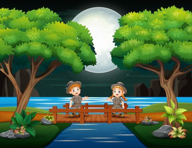 Junge pfadfinder, welche die holzbrücke kreuzen