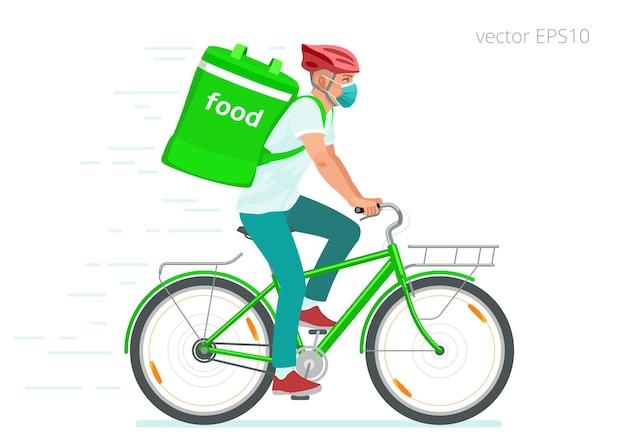 Junge radfahrer mit medizinischer maske liefern während der covid-sperrung ein warmes essen