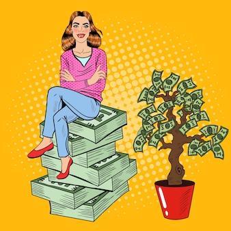 Junge reiche pop-art-frau, die auf einem geldstapel nahe geldbaum sitzt. illustration