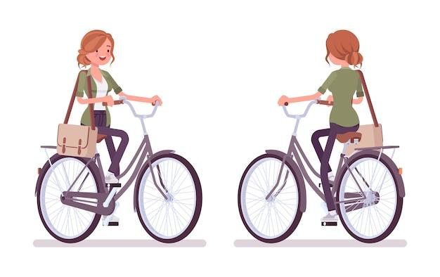 Junge rothaarige frau, die fahrrad fährt