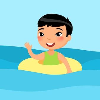 Junge schwimmt mit aufblasbarem ring. schönes kind, das spaß im wasserwinken hat, kind, das sommeraktivitäten genießt