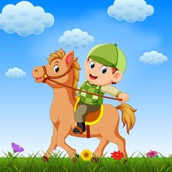 Junge, steig ins pferd und spiel mit ihm auf dem feld