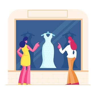 Junge stilvolle frauen stehen am schaukasten, der auf modischem kleid im laden schaut. karikatur flache illustration