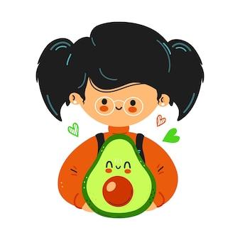 Junge süße lustige kleine mädchen halten avocado in der hand