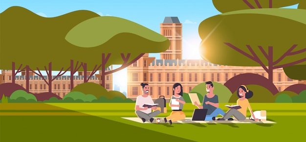 Junge teenager-studentengruppe, die auf gras am campushof-bildungskonzept college-freunde sitzen, die sich entspannen und vor dem universitätsgebäude außen horizontal in voller länge sprechen