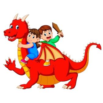 Junge und das mädchen, das mit dem großen roten drachen und dem jungen hält das schwert spielt