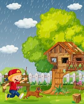 Junge und hund, die in den park am regnerischen tag laufen