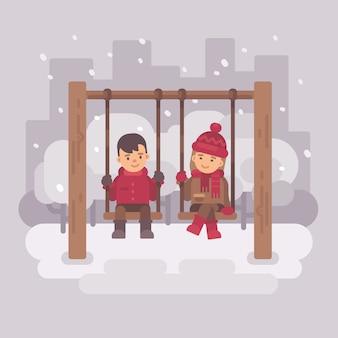 Junge und mädchen auf schwingen in einem winterstadtpark