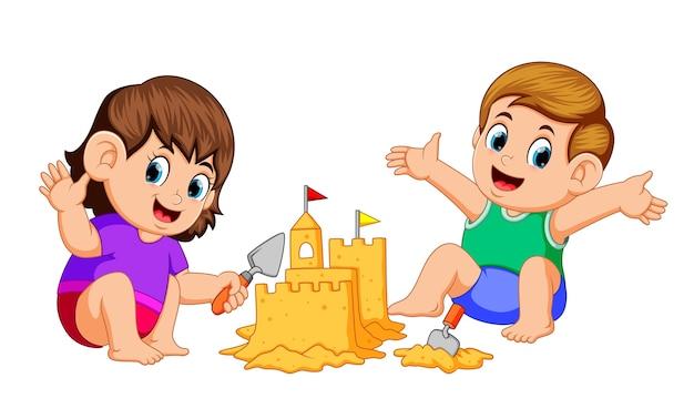 Junge und mädchen, die eine große sandburg am strand machen