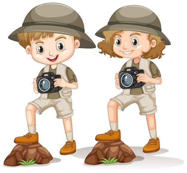 Junge und mädchen im safari-outfit mit kamera, die auf dem felsen steht