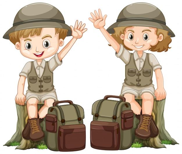 Junge und mädchen in der safariausstattung, die auf klotz sitzt