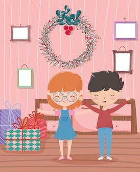 Junge und mädchen mit geschenkkranz gestaltet feier der frohen weihnachten des wohnzimmers