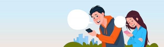 Junge und mädchen-mitteilung, die draußen handy-social media-kommunikations-lebensstil halten hält