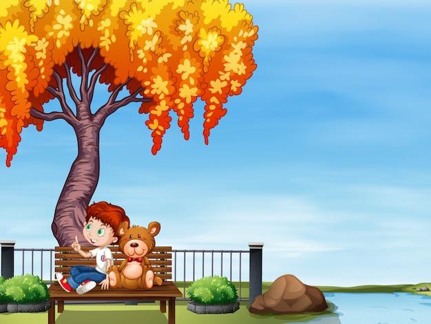 Junge und teddybär im park