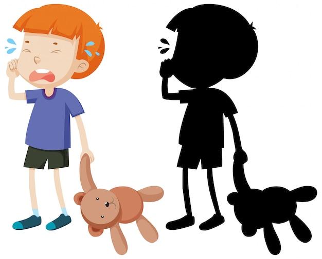 Junge weint und hält teddybär mit seiner silhouette
