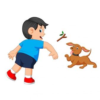 Junge wirft seinem hund einen stock