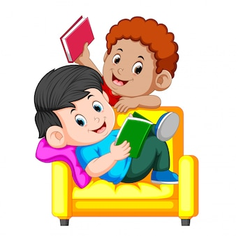 Junge zwei liest ein buch, das auf einem großen bequemen stuhl sitzt