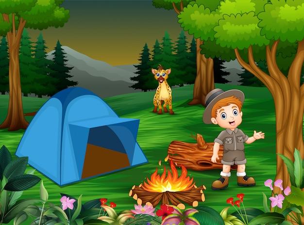 Jungen im campingoutfit mit hyäne auf dem campingplatz