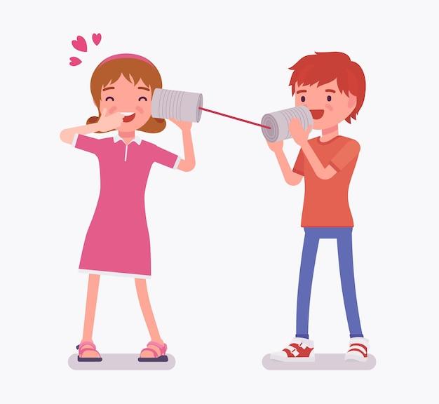 Jungen und mädchen, die mit blechdose telefonieren