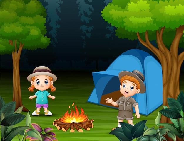 Jungen und mädchen stehen auf einem campingplatz