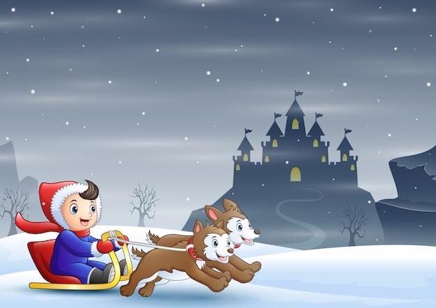 Jungenreitschlitten auf dem schnee, der von zwei hunden gezogen wurde