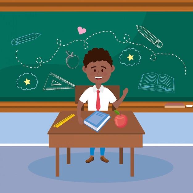 Jungenstudent im schreibtisch mit apfelfrucht und buch