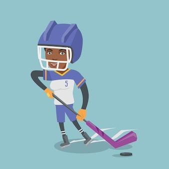 Junger afrikanischer eishockeyspieler mit einem stock.