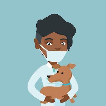 Junger afrikanischer tierarzt mit hund in den händen.
