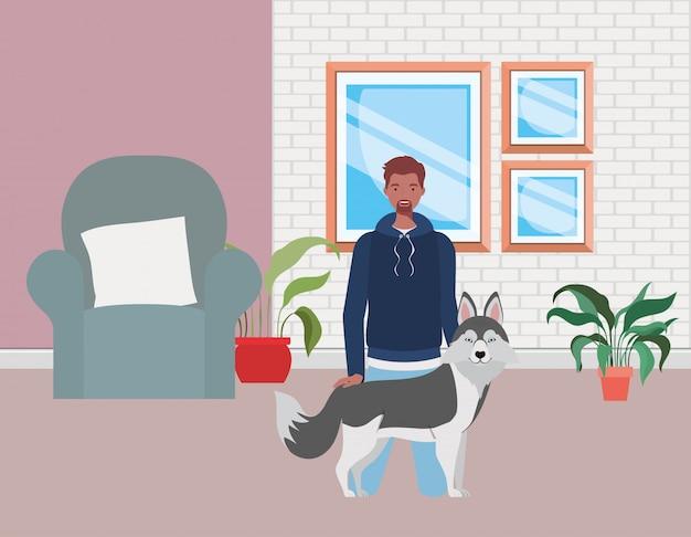 Junger afromann mit nettem hundemaskottchen im wohnzimmer