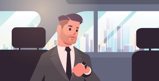 Junger geschäftsmann, der auf uhr schaut, der geschäftsmann-autopassagier auf dem rücksitz im taxi-stadttransportdienst sitzt