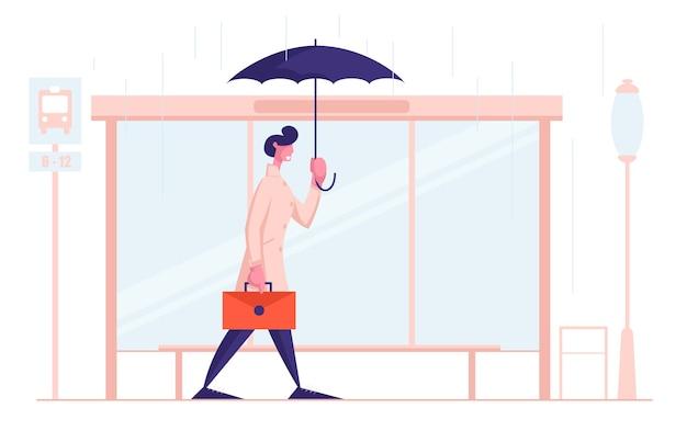 Junger geschäftsmann-stadtbewohner mit regenschirm und aktentasche stehen am busbahnhof im regen