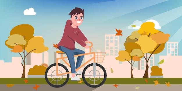 Junger glücklicher mann fährt im herbst fahrrad