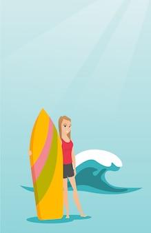 Junger kaukasischer surfer, der ein surfbrett anhält.