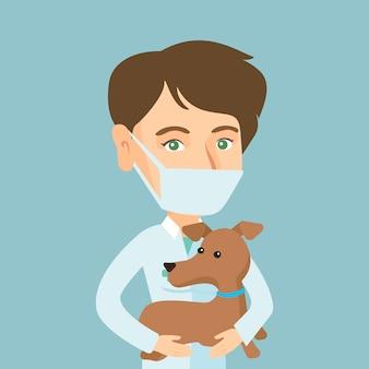 Junger kaukasischer tierarzt mit hund in den händen.