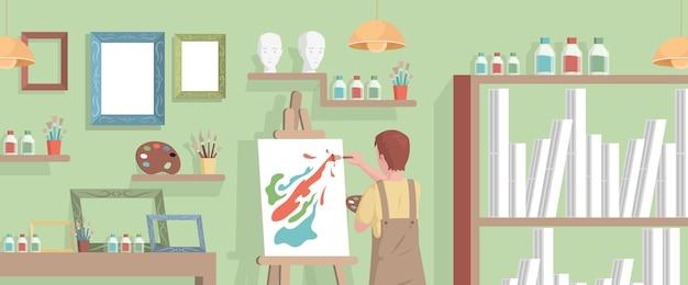 Junger künstler, der abstraktes bild auf leinwand im kunststudio zeichnet