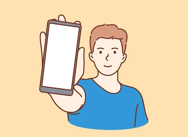 Junger lächelnder mann, der smartphone-bildschirm mit weißem modell für text oder beschriftung zeigt