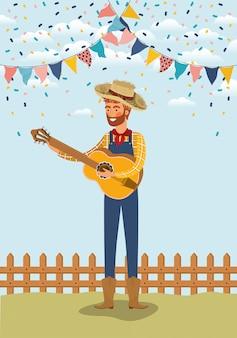 Junger landwirt, der gitarre mit girlanden und zaun spielt