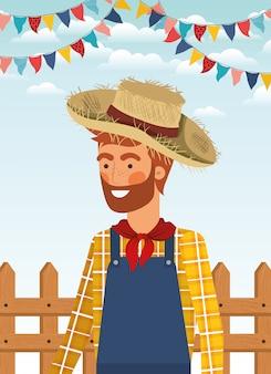 Junger landwirt, der mit girlanden und zaun feiert