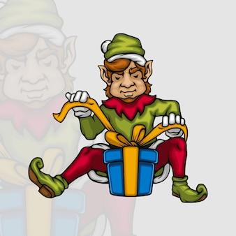 Junger männlicher elf, der eine weihnachtsgeschenkbox mit einem band verziert