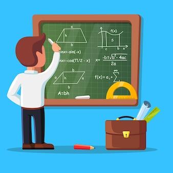 Junger männlicher lehrer auf lektion an der tafel im klassenzimmer. schullehrer, der matheformeln an tafel schreibt.