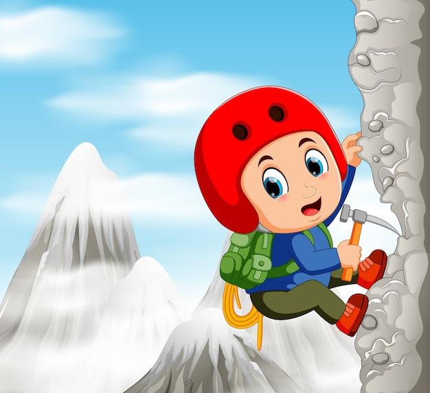 Junger mann beim klettern des schwierigen weges auf klippe