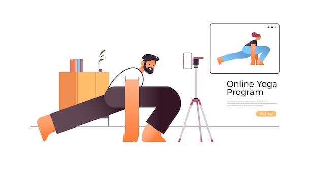 Junger mann, der dehnübungen macht, während online-video-trainingsprogramm mit weiblichem yogalehrer-trainingskonzept in voller länge horizontale kopie raum illustration