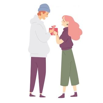 Junger mann, der einen frauenpräsentkarton, mädchen empfängt ein geschenk von einem jungen gibt.