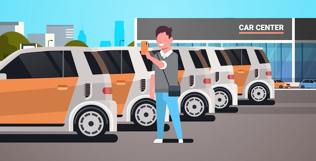 Junger mann, der fahrzeug auf parkplatz des autozentrums unter verwendung des carsharing-konzepttyps der mobilen anwendung wählt, der smartphone-online-autovermietungsdienst hält