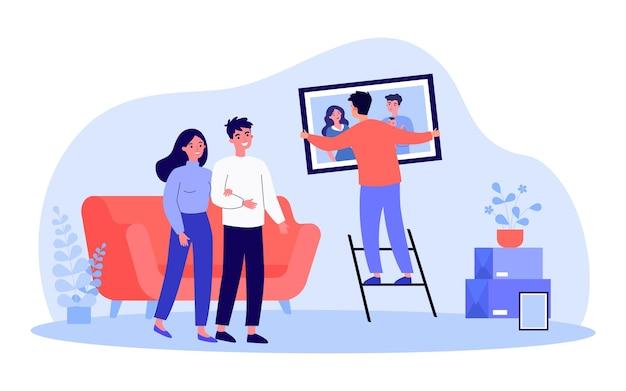 Junger mann, der familienporträt an der wand hängt. flache vektorillustration. paar beobachten mann, der hilft, indem er ein gerahmtes foto an der wand im wohnzimmer aufhängt. familie, fotografie, service, dekorationskonzept