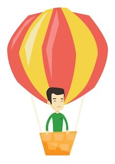 Junger mann, der im heißluftballon fliegt.