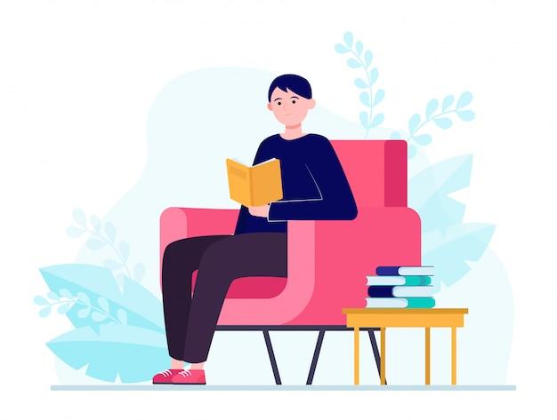 Junger mann, der im sessel sitzt und buch liest