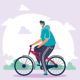 Junger mann, der medizinische maske im fahrrad trägt
