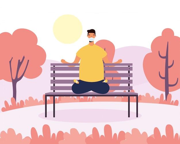 Junger mann, der medizinische maske trägt, die yoga im parkstuhl praktiziert