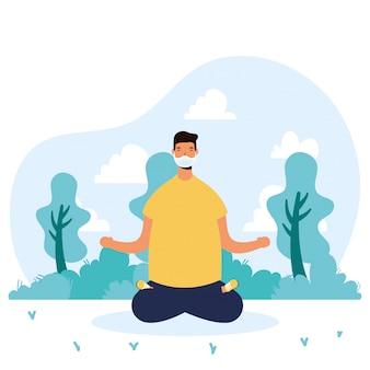 Junger mann, der medizinische maske trägt, die yoga praktiziert